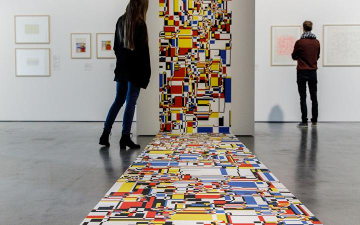 A mosaic of colored surfaces extends from the wall to the floor