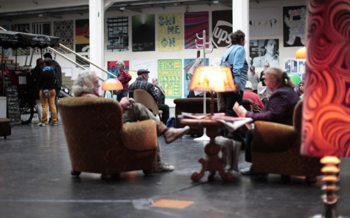 Menschen sitzen auf Wohnzimmermöbeln und lesen Zeitung