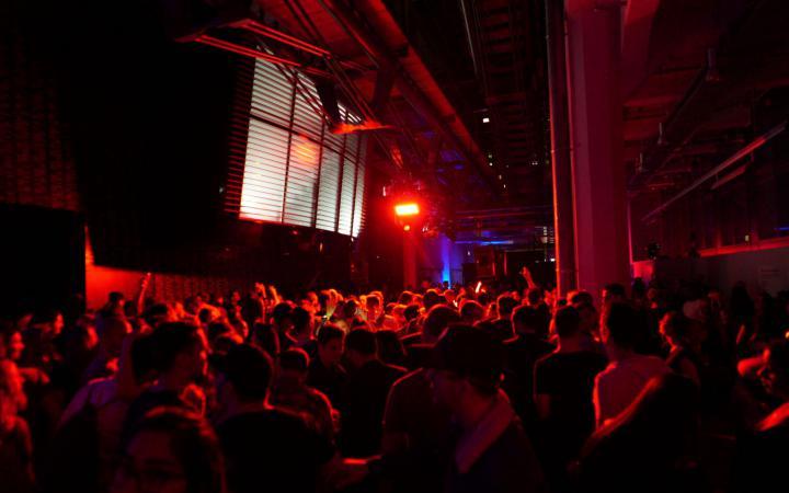 Das Foto zeigt den Gang des ZKMs in Richtung HfG in einem tiefen rot erleuchtet mit vielen tanzenden Menschen, die wie ein großer Körper durch das verschwommene Licht wirken.