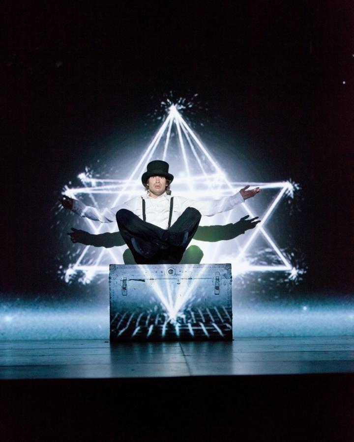 Ein Mann mit Zylinder sitzt auf einem leuchtenden Sockel, im Hintergrund ein leuchtender Stern