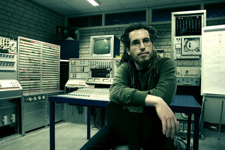 Ein Mann mit Dreadlocks und Brille sitzt vor technischem Equipment wie PCs, Lautstärkereglern und weiteren Monitoren