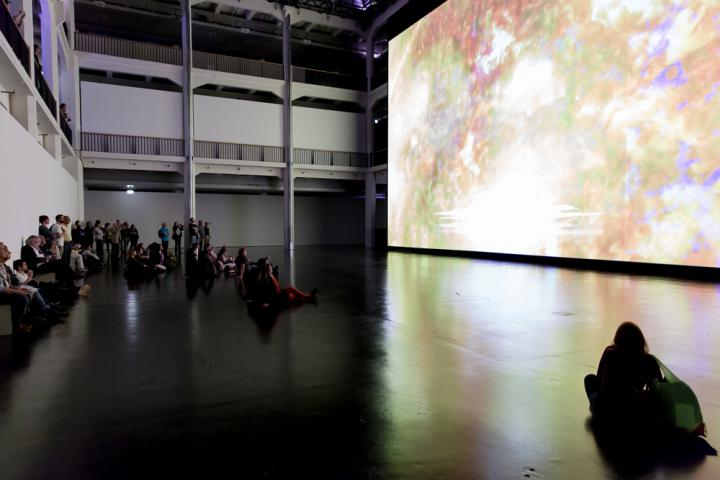 People sitting in front of a huge canvas