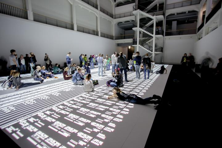 People sitting, lying and standing on a huge projection