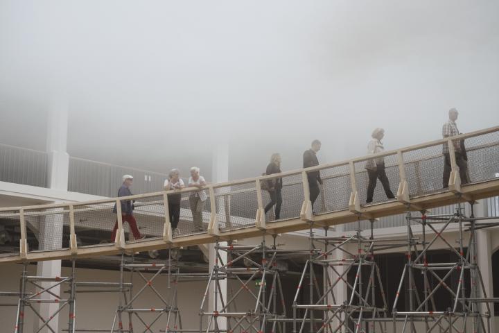Personen laufen über eine Rampe in eine Wolke