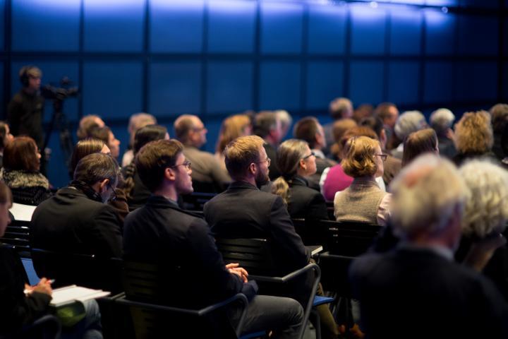 Viele Menschen sitzen in einem Saal. Man sieht sie von hinten.