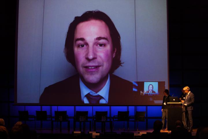 Ein sprechender Mann auf einem Screen sowie drei Männer auf einer Bühne.