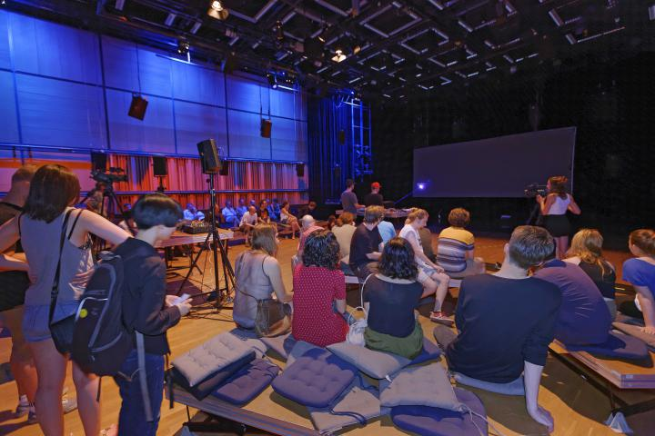 People sitting on the ground in front of a stage