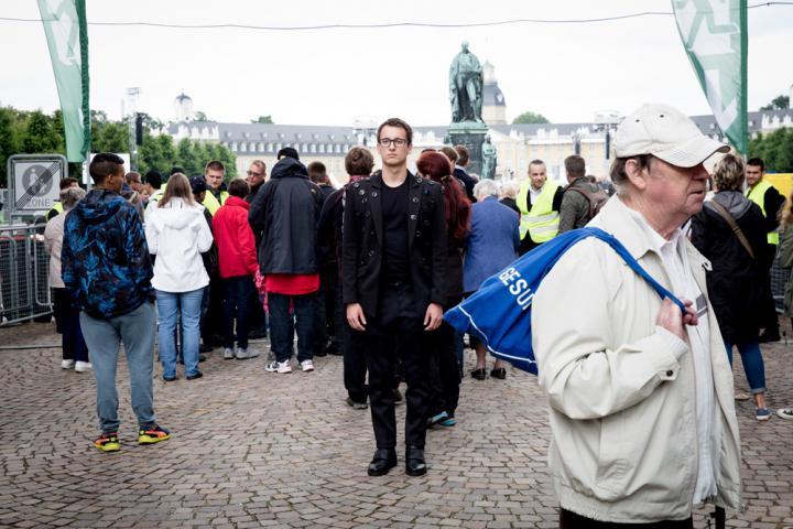 Eine Person auf dessen Jacke viele Kameras sind steht in einer Menschenmenge