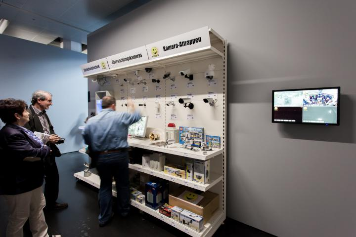 Zwei Männer stehen vor einer Tafel, an der verschiedene Überwachungskameras hängen