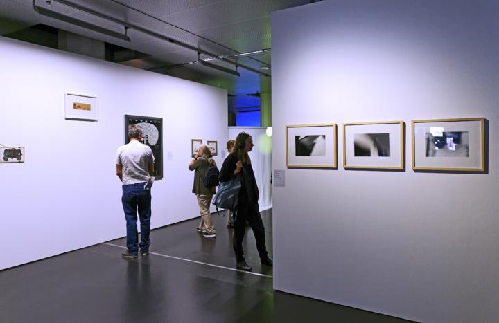 Leute betrachten Gemälde an der Wand