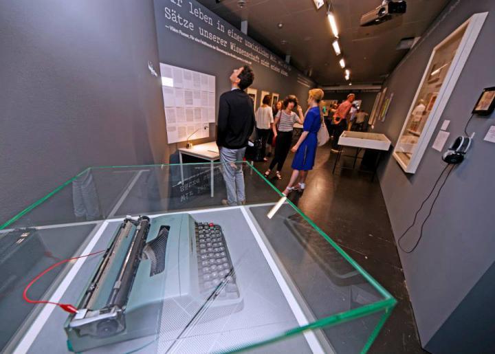 Menschen stehen im Ausstellungsraum und betrachten die Werke