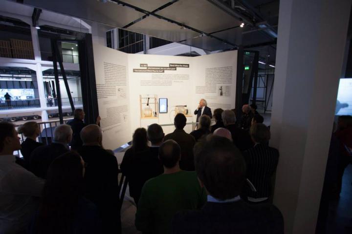 Ein Mann steht vor einer großen Tafel und spricht zu dem Publikum