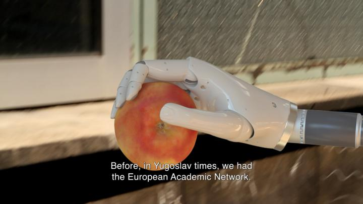 A roboter hand holds an apple
