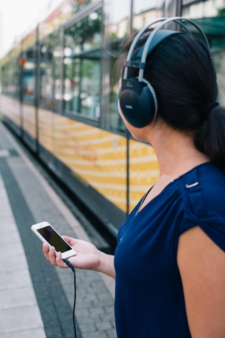 A woman with headphones and mobile in front of a tram