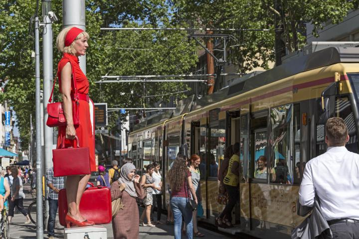 A woman in red is standing on a power box in the middle of the pedestrian zone