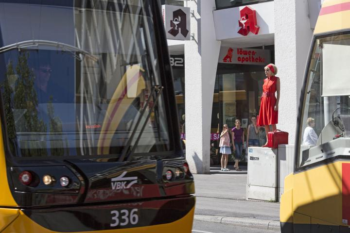 Eine Frau in Rot steht auf einem Stromkasten mitten in der Fußgängerzone