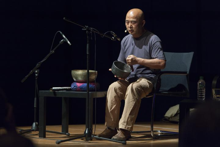A man with a singing bowl on stage