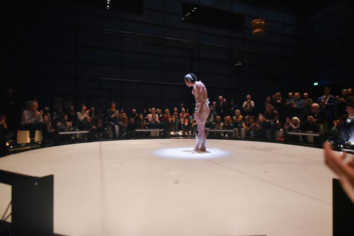 A male person bows and is wrapped in a kind of plastic film