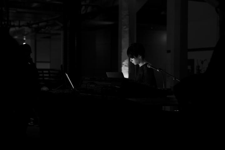 Eine Frau steht hinter ihrem Mischpult zwischen hohen Lautsprechersäulen