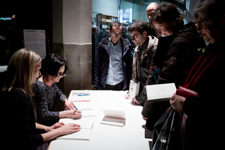 People standing in front of a desk. A woman sitting at the desk signing books