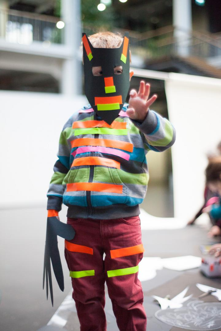 A boy with a homemade mask and various strips on clothing