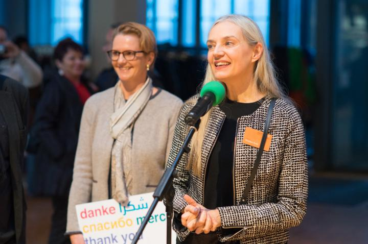 Two women stand in front of a microphone