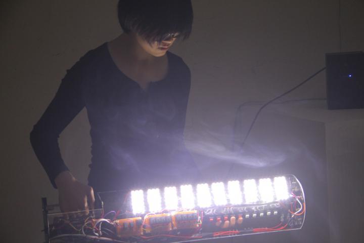 Eine Frau an einem selbstgebauten, leuchtenden Instrument