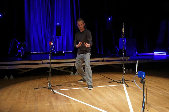 A man stands in a with tape drawn triangle