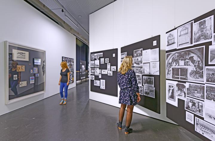 Two women are looking at the panels of Aby Warburg