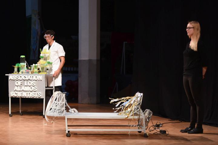 Ein junger Mann mit Kittel und Brille steht an einem Tisch mit Apparaten. Rechts davon eine Trage und dahinter eine junge Frau