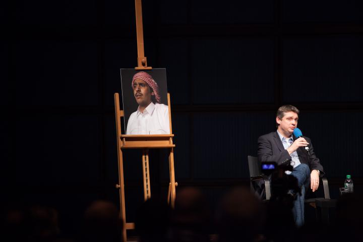 On an easel is a picture of a man with a turban