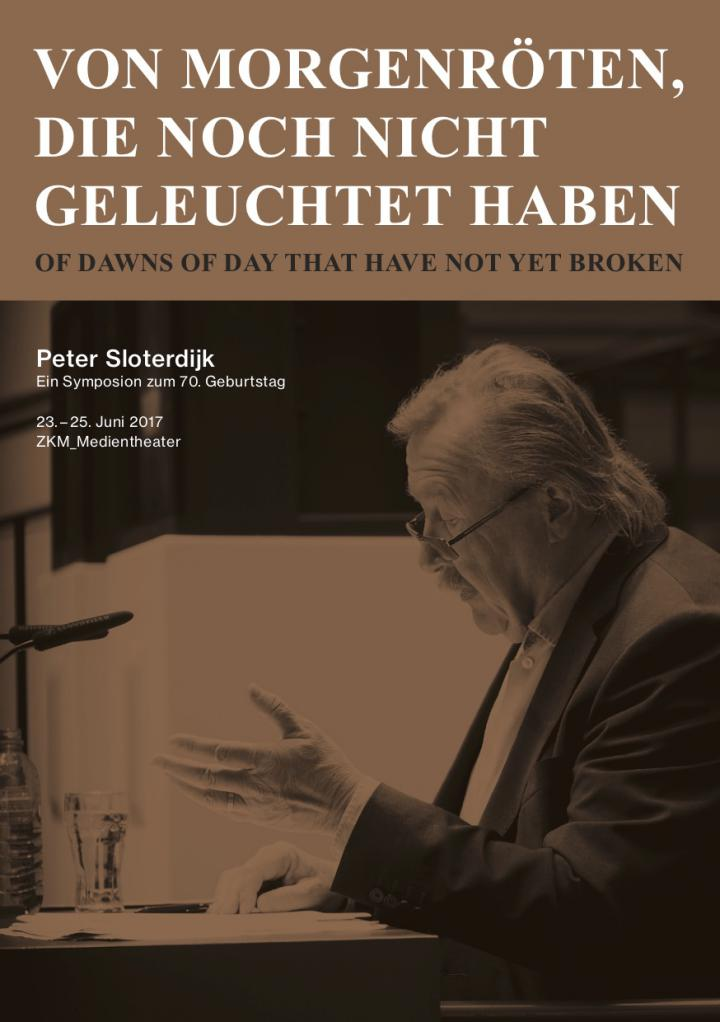 Photo of Peter Sloterdijk during a lecture, sitting at a table.