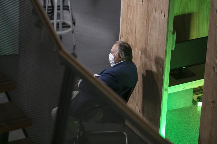 Peter Weibel sitzt mit einer Mund-Nasen-Schutz-Maske auf einem Stuhl und schaut aus dem Bild raus.