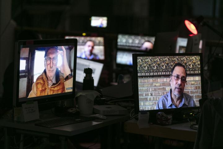 Mehrere kleine Bildschirme zeigen die Gesichter von Bruno Latour und Dipesh Chakrabarty.
