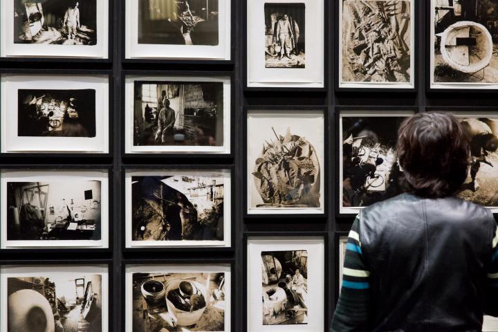 Das Foto zeigt die Rückenansicht eines Mannes vor mehreren Schwarz-Weiß-Fotografien Tambellinis