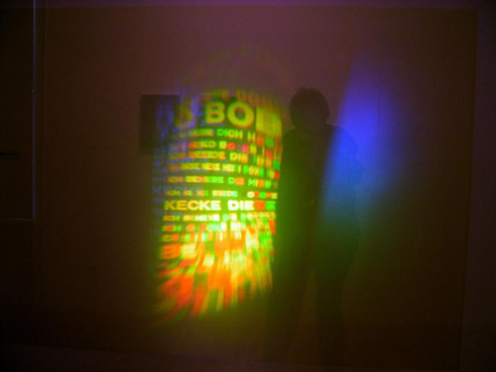 Das Bild zeigt eine grün-gelbe Lichtinstallation mit Buchstaben.