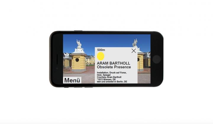 Zu sehen ist eine Animation eines Smartphones. Das Smartphone zeigt auf dem Display das Karlsruher Schloss. Vor dem Bild des Schlosses ist ein geöffnetes Pop-Up-Fenster, das Informationen zu einem Kunstwerk in der Nähe liefert.