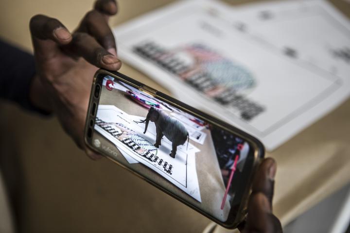 Auf einem Handydisplay erscheint ein Elefant in Augmented Reality