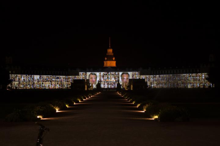 Die Fassade des Karlsruher Schlosses bespielt mit vielen Passbildern verschiedener Personen.