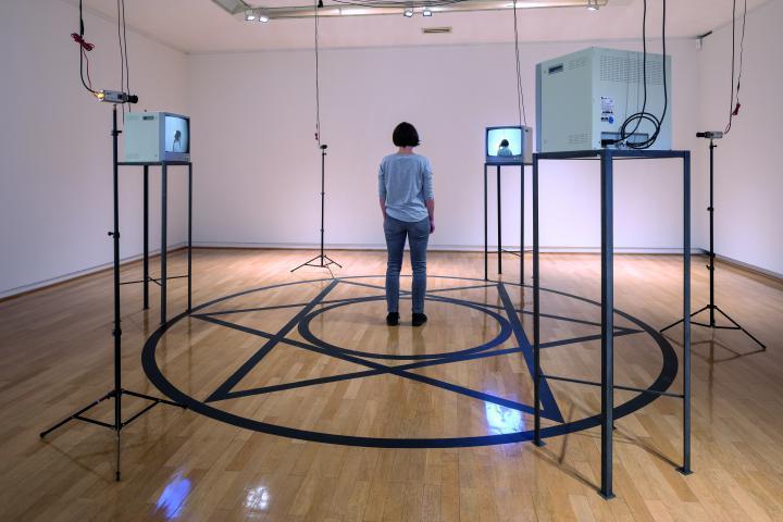 Zu sehen ist ein Raum, in dem vier Monitore auf einem Gestell stehen. Auf dem Boden ist ein Kreis aufgeklebt, in dessen Mitte ein Stern sowie noch ein Kreis ist. In der Mitte steht eine Frau mit dem Rücken zum Betrachter.
