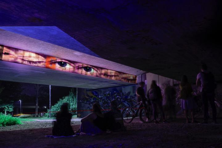 Eine Brücke in einem Park bei Nacht. An die Außenwand der Brücke ist in einem horizontalen Streifen eine Reihe Augenpaare projiziert. Der Rets der Brücke leuchtet in verschiedenen Farben.