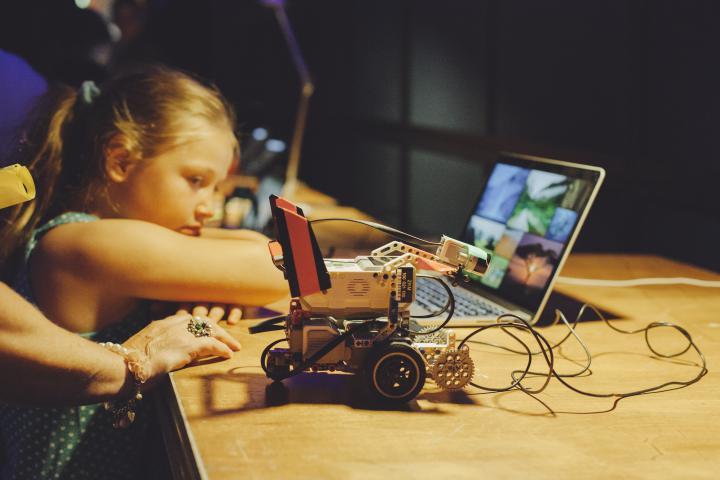 Ein Kind lehnt an einen Tisch, auf dem ein kleiner Roboter steht