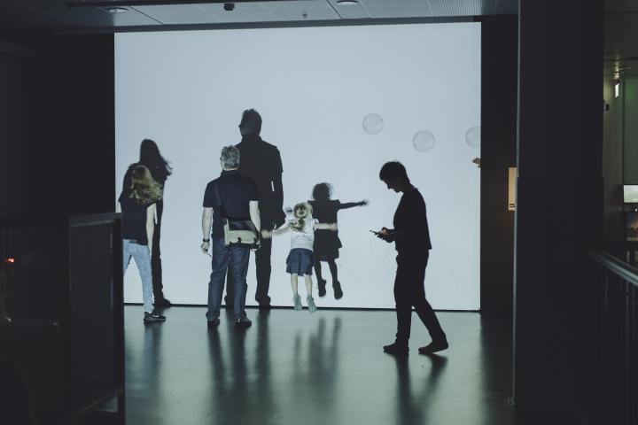 Museumsbesucher bewegen sich vor einer Leinwand mit Seifenblasen