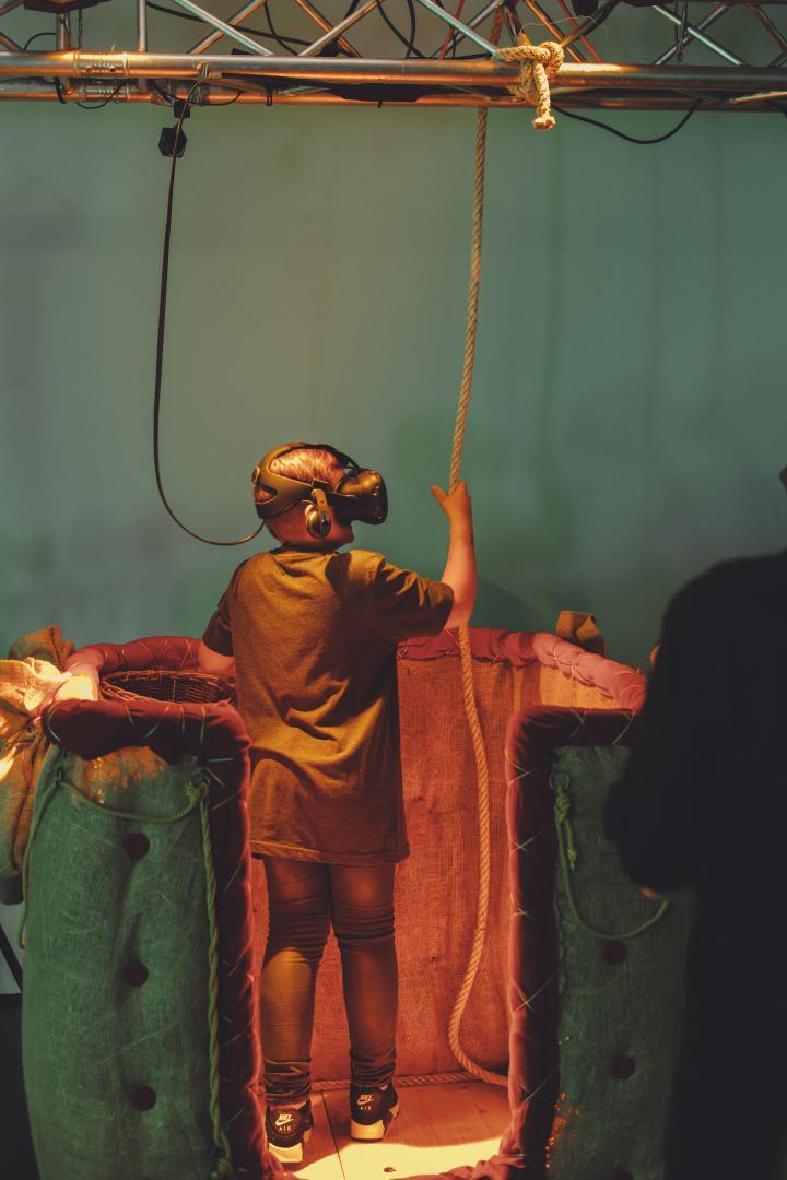Ein Kind, das eine VR-Brille trägt, steht in einem Heißluftballonkorb