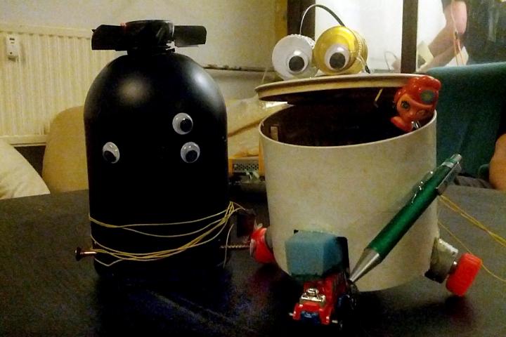 Zwei kleine Roboter aus Schrott stehen nebeneinander, der eine ist schwarz und hat 3 Augen, der andere besteht aus einem Eimer und hat zwei Augen aus Flaschendeckeln, die auf dem geöffneten Mund bzw dem Deckel angebracht sind.
