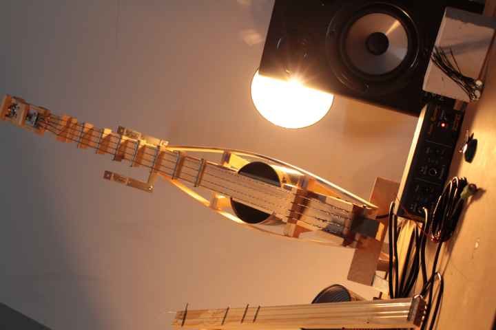A diy guitar out of thin wood and a tin can is standing upright next to a speaker. A bright light is shining on the instrument from behind.