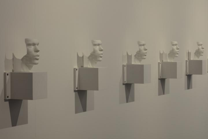 Several busts - 3D prints of the artists' vocal bands - hang side by side on a wall.