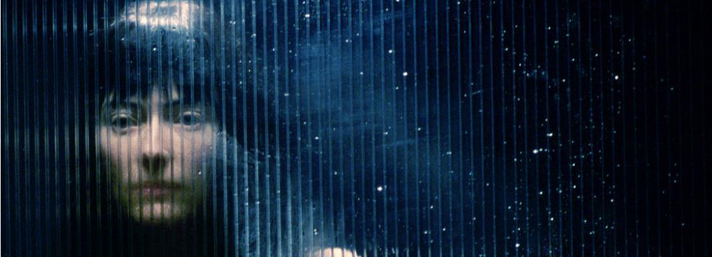Eine Frau schaut durch eine durch Regen verwischte Scheibe