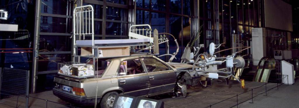 Ein Auto, auf dessen Dach ein Bettgestell steht. Über dem Auto hängt ein überdimensionales, hell-blaues Herz, welches mit Eisenstangen und Schlössern versehen ist.