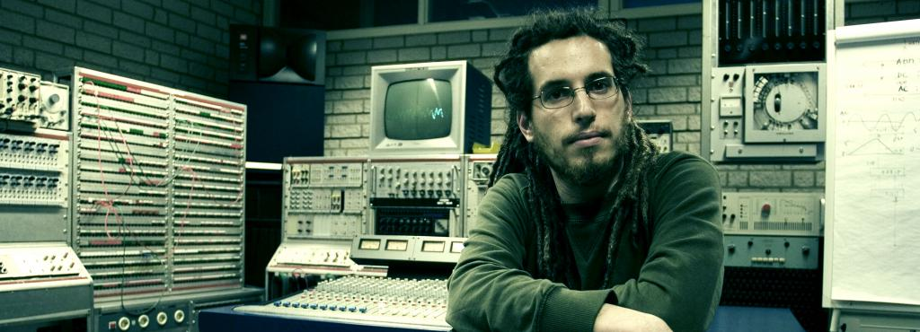 A man with dreadlocks and glasses sitting in front of technical equipment such as PCs, volume controls and other monitors